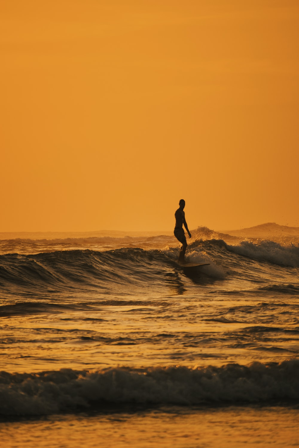 silhouette of person riding on white surfboard