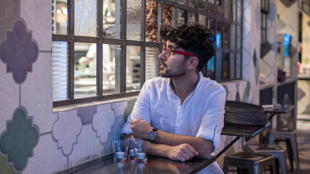 man wearing white dress shirt sitting beside table