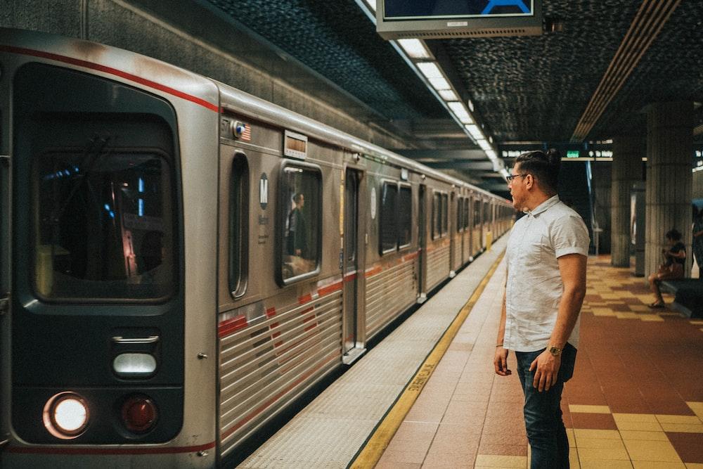 man wearing white dress shirt standing near gray train