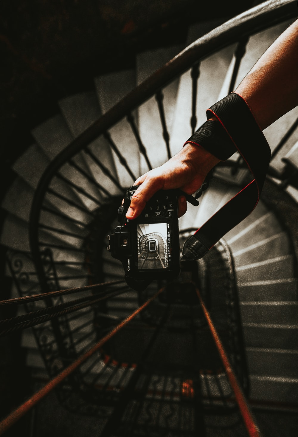 person holding black DSLR camera taking photo of spiral stairs