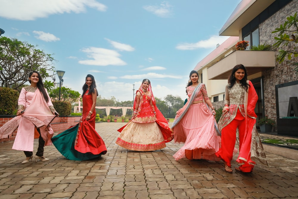 five women wearing red dress standing on pavement
