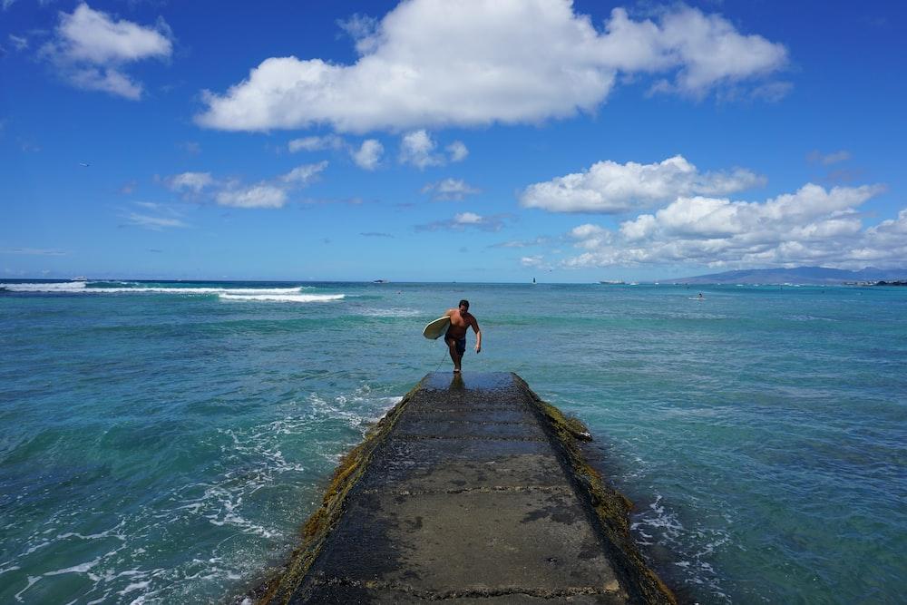 man walking on dock holding surfboard