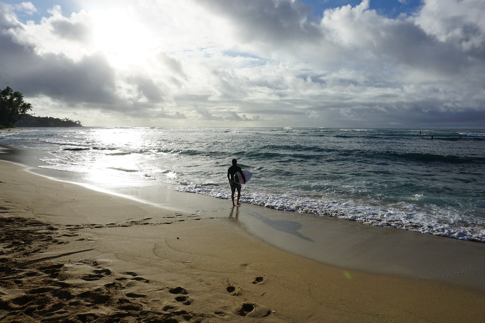 person walking on seashore holding white surface