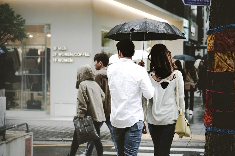 standing man wearing white dress shirt beside woman