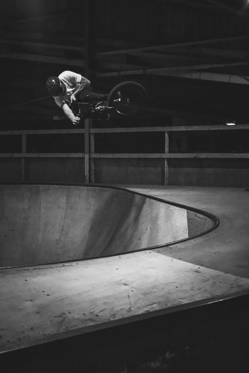 grayscale photo of person riding BMX bike