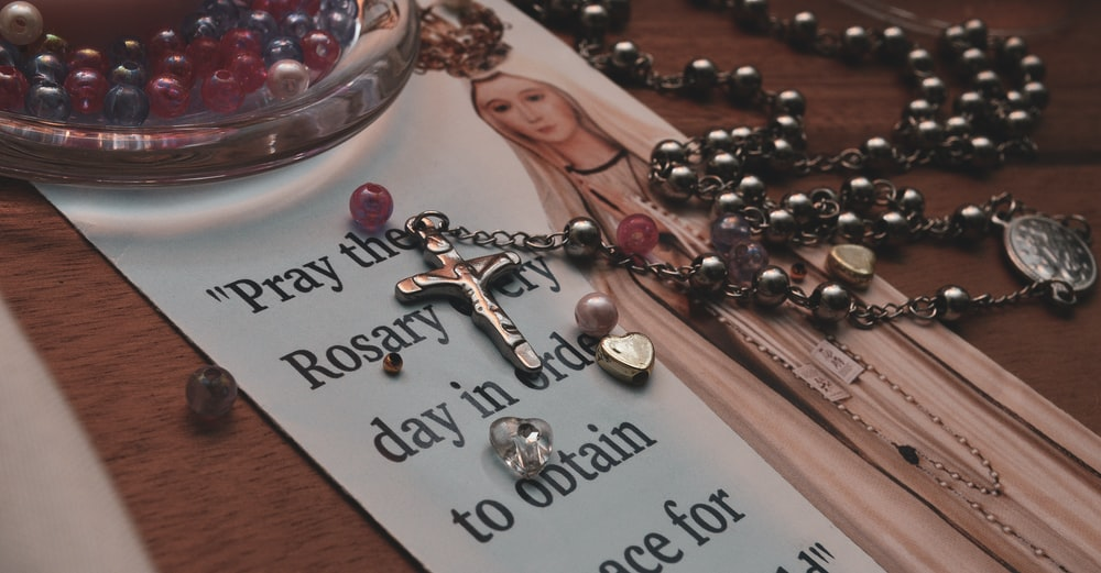 silver and black rosary on nun graphic paper