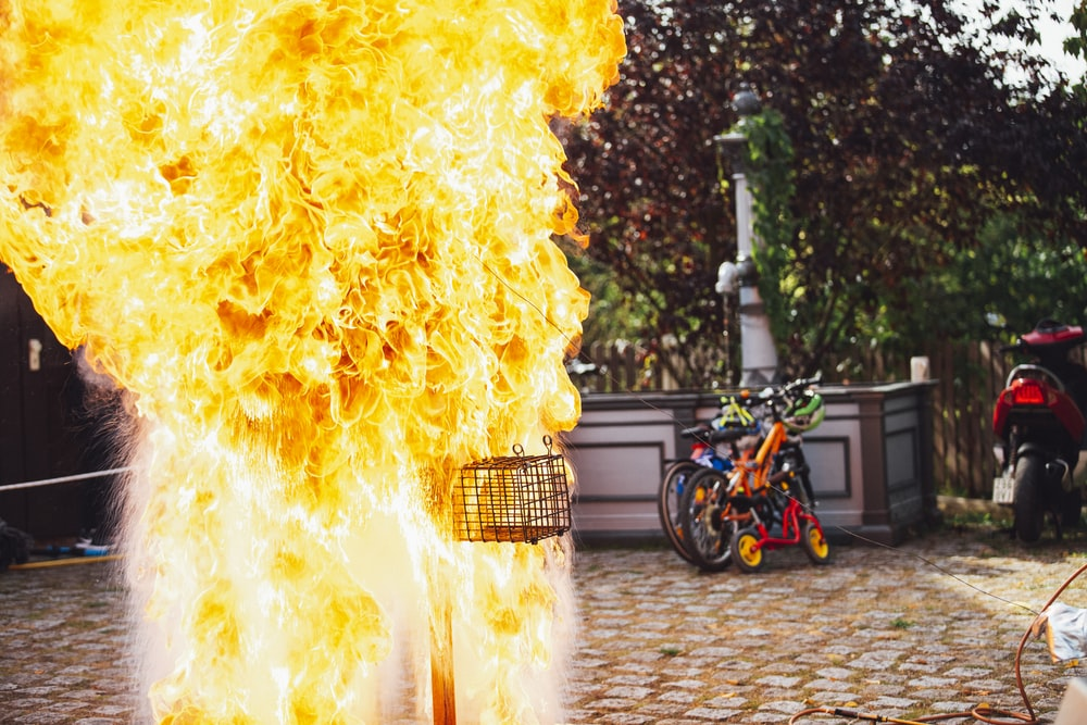 two bikes parking near wall beside big fire