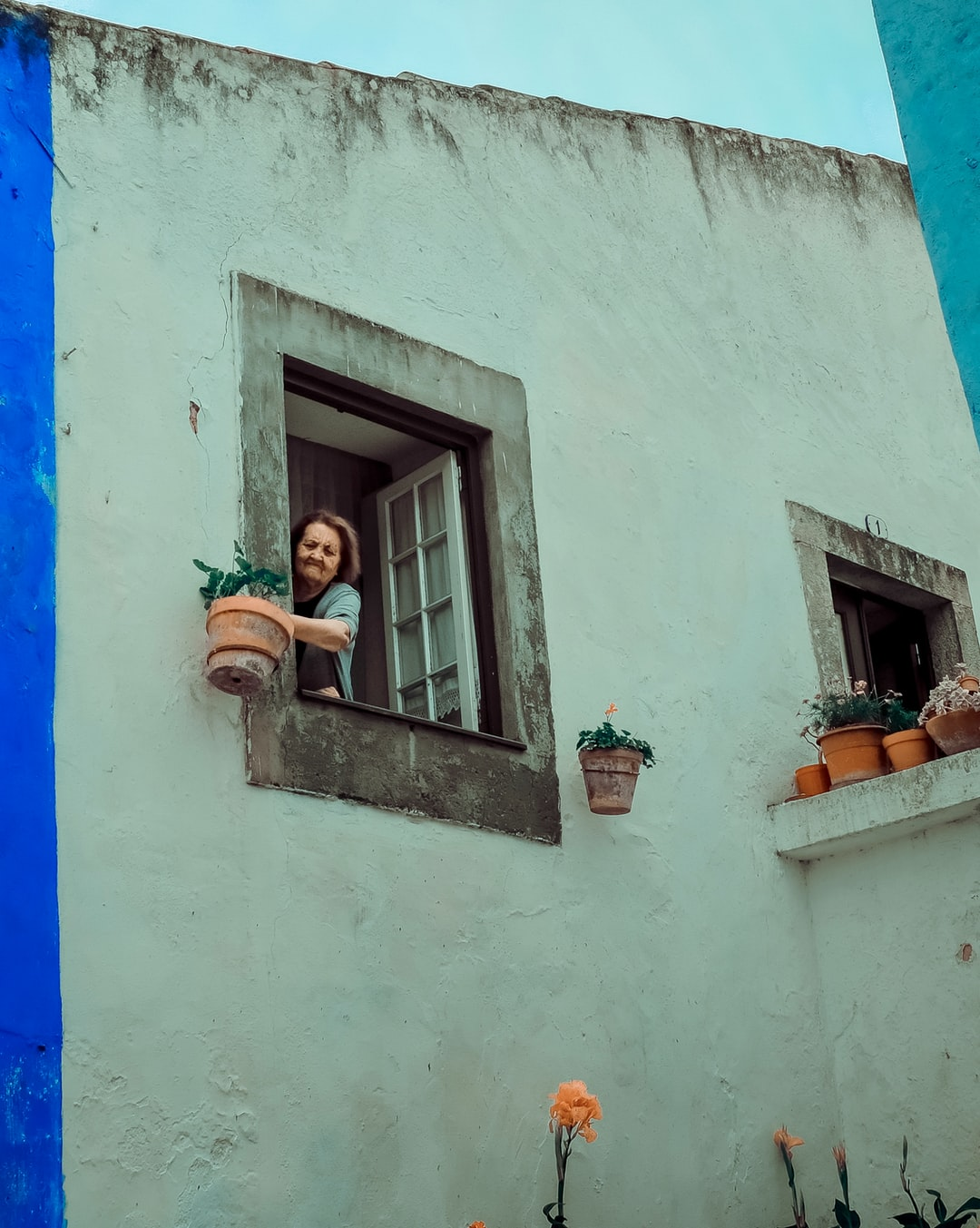An elderly lady watering her plants in Obidos, Portugal.