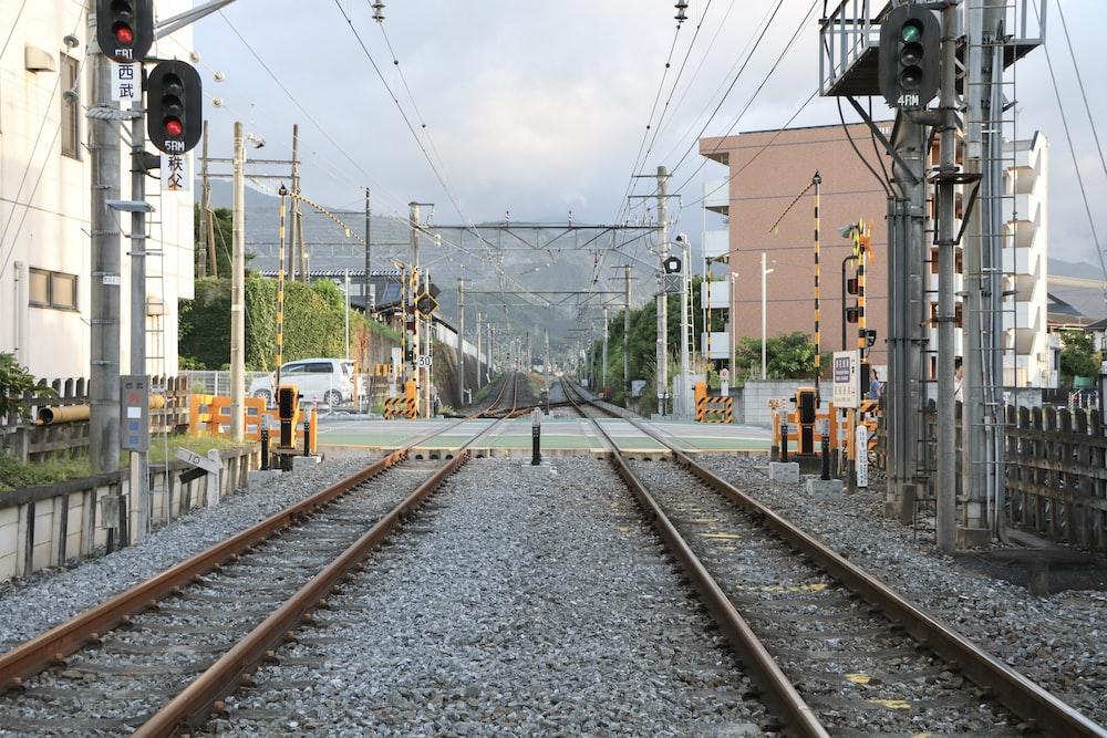 empty brown train rails under blue sky