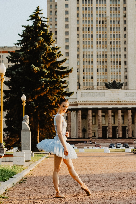 ballerina standing on pathway near buildings