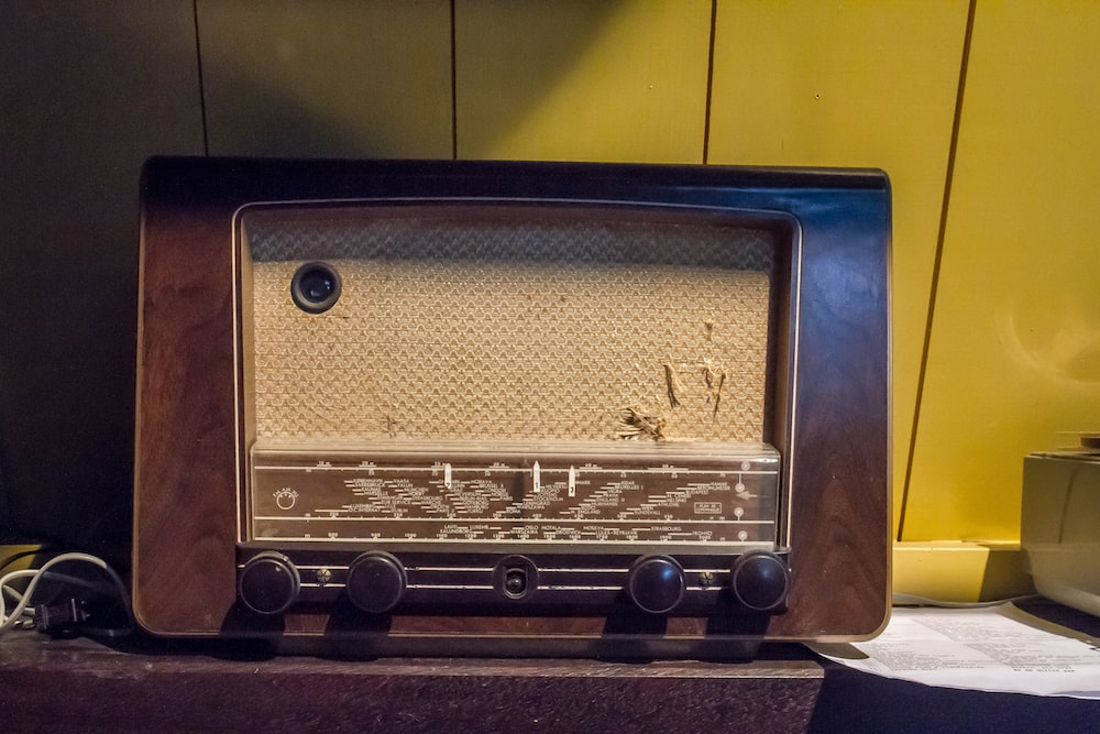 brown and gray transistor radio beside wall
