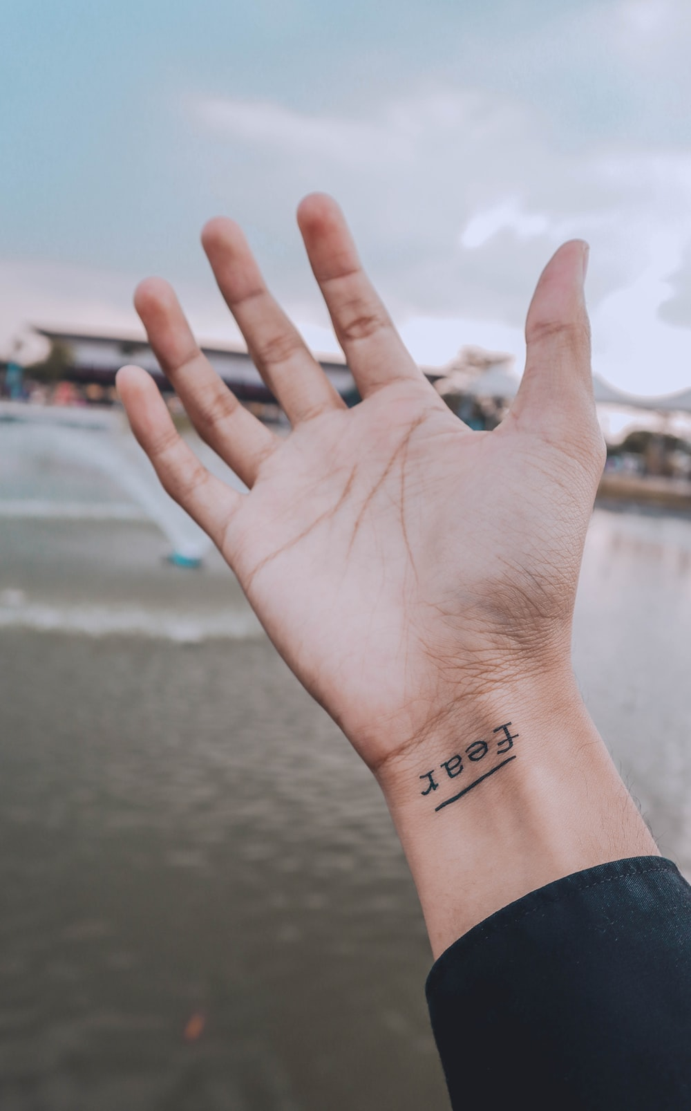 person showing right wrist with fear tattoo