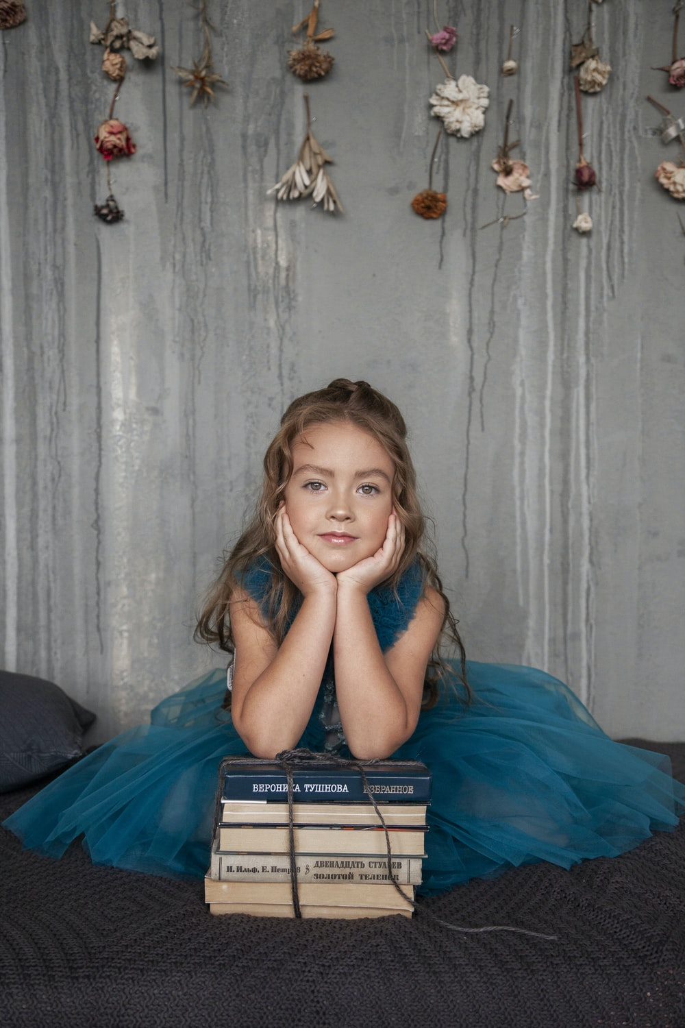 girl in blue dress resting head on both hands while leaning on piled book
