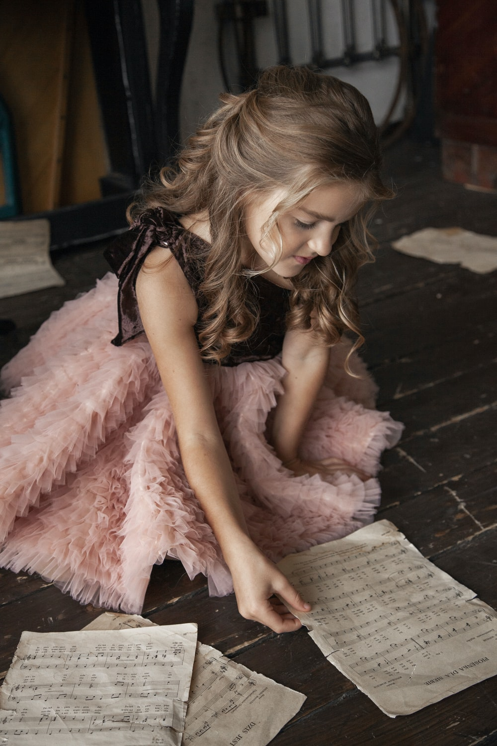 crouching girl wearing pink and black dress holding sheet