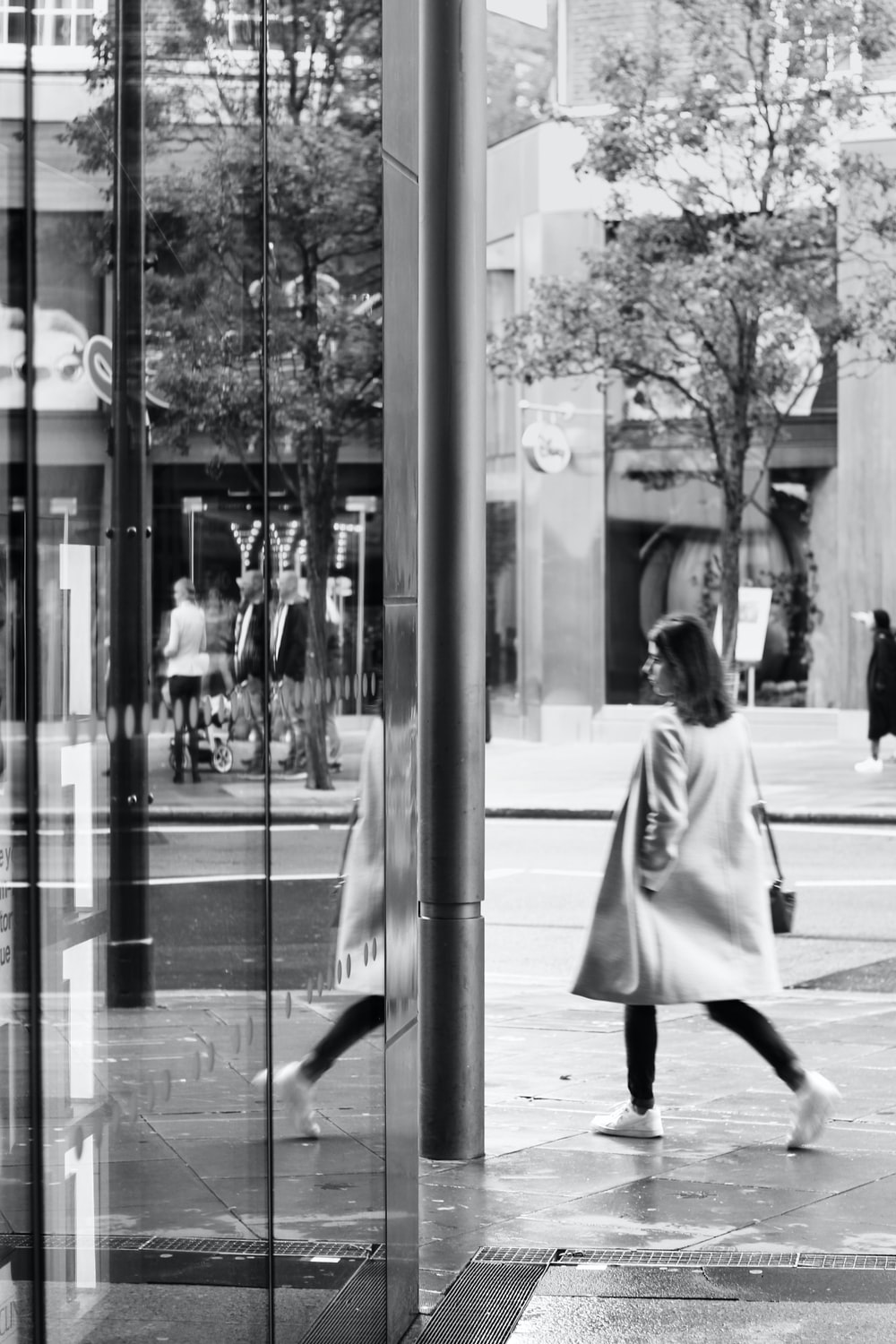 grayscale photo of woman in overcoat