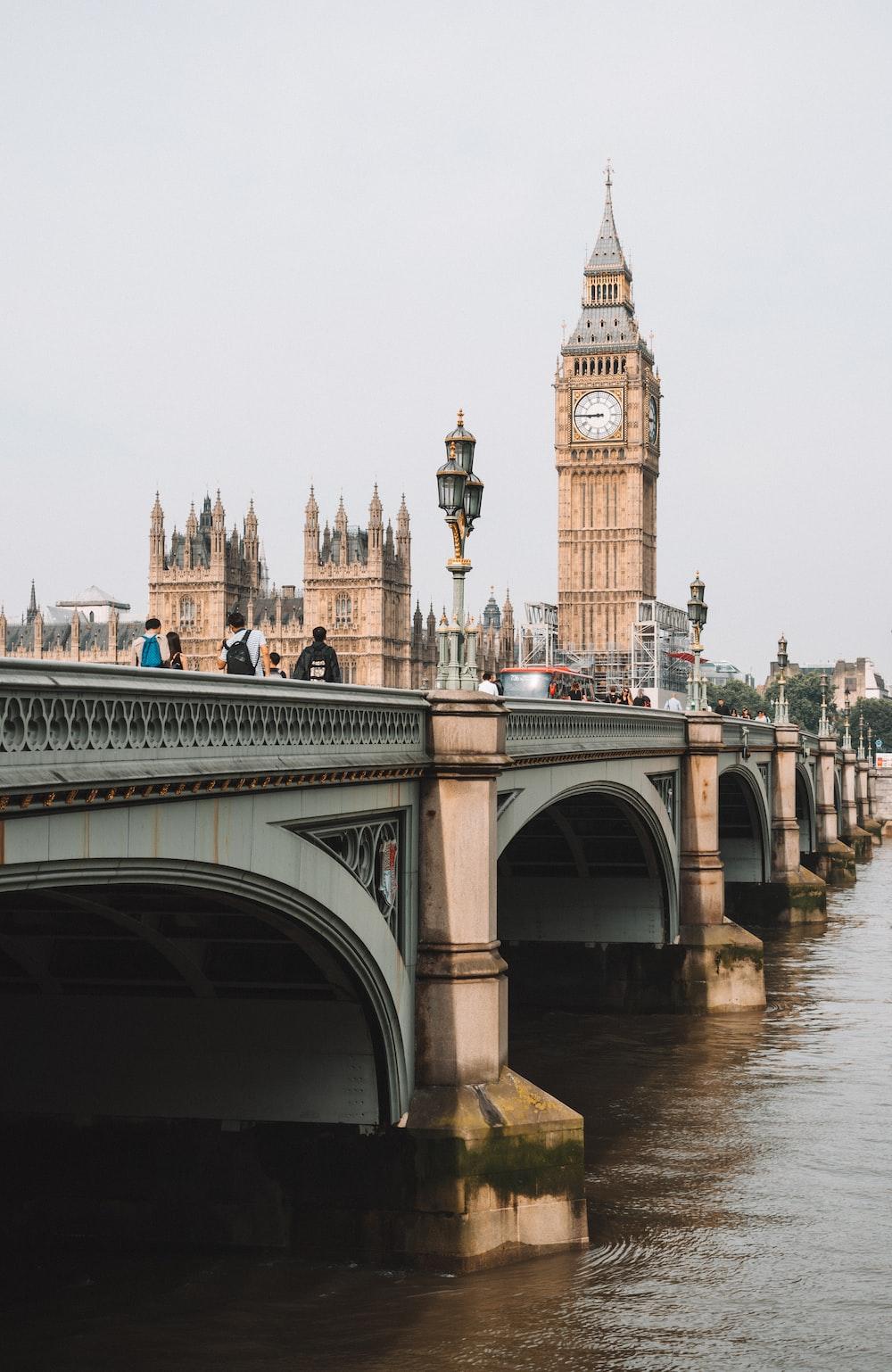 people on bridge near Queen Elizabeth tower under gray skies