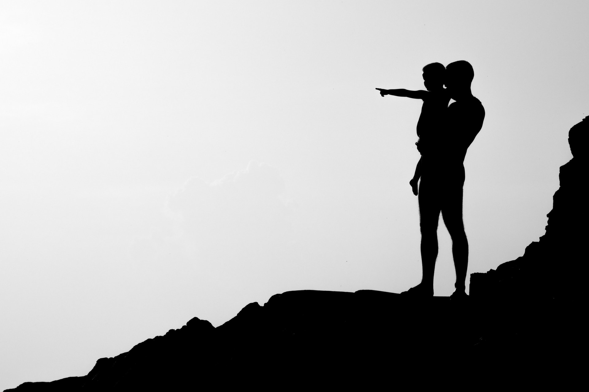 silhouette of man carrying child