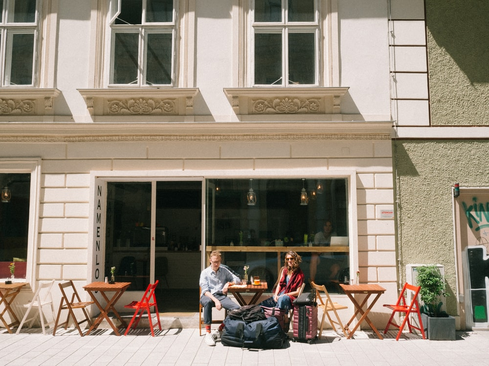 two people sitting on chair beside store