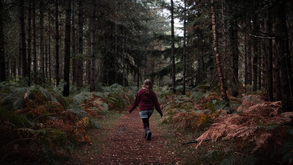 woman in red hoodie standing between trees