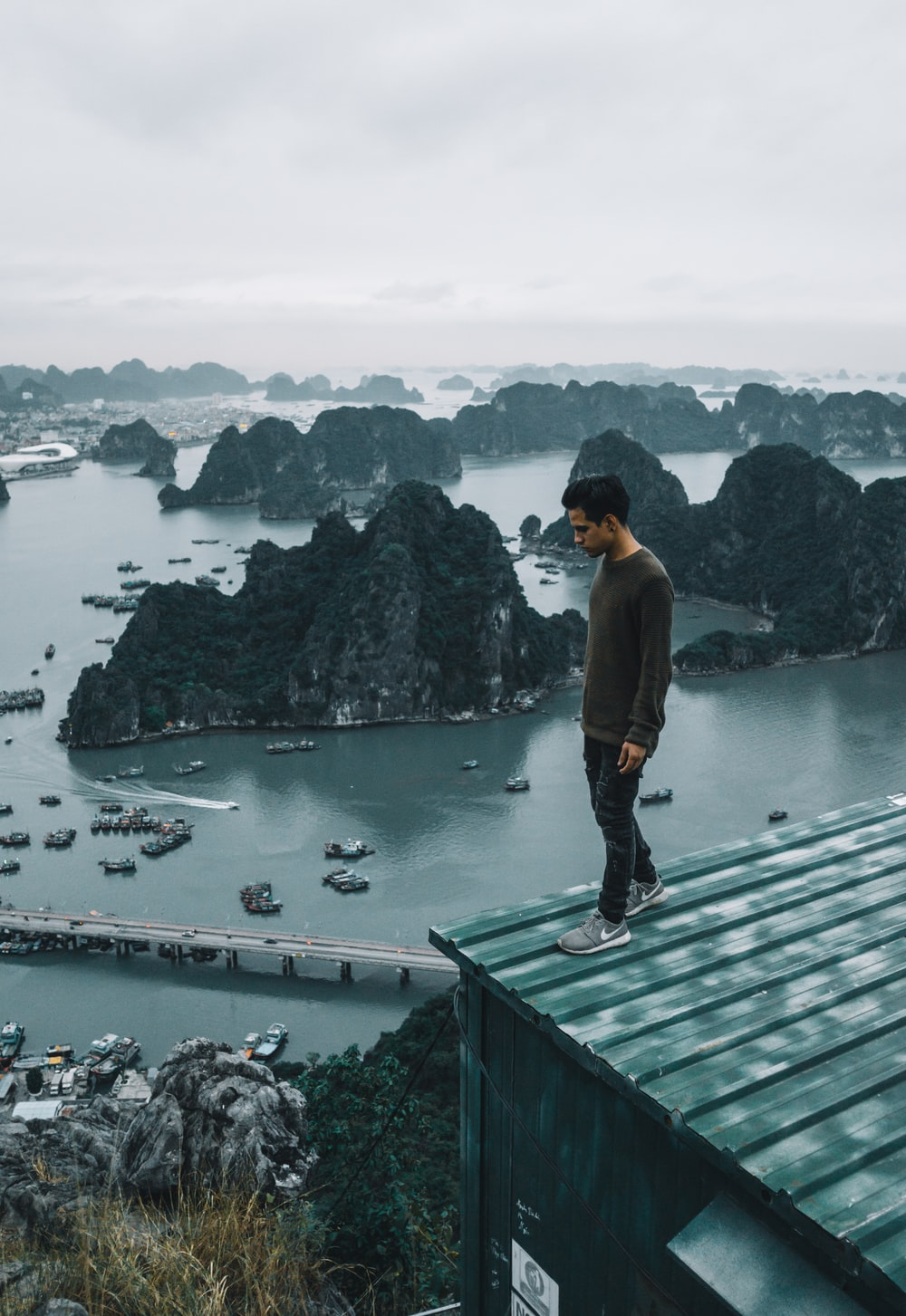 man wearing gray sweater standing on rooftop