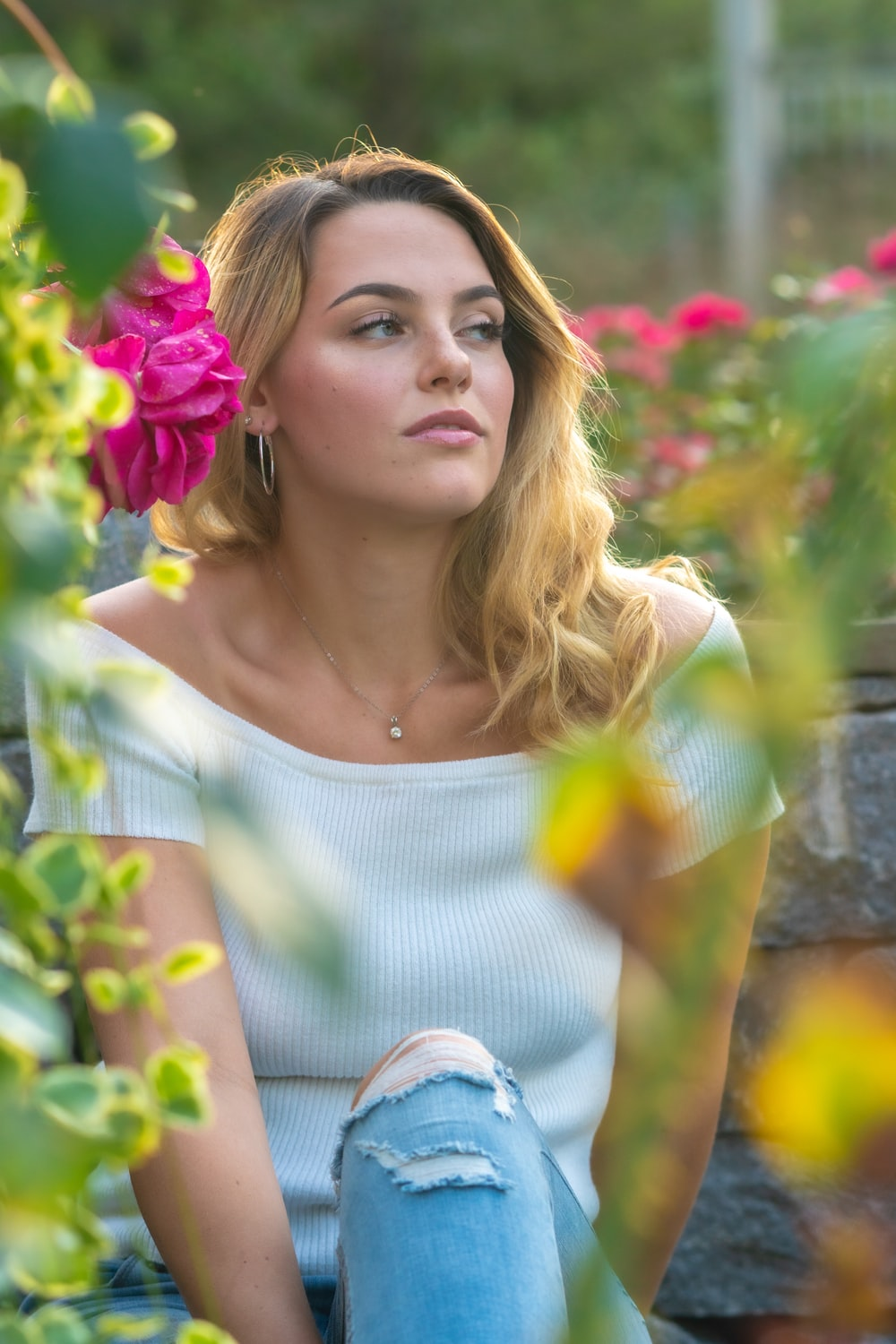 woman in white top sitting near pink flowers