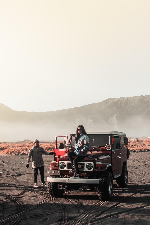 woman sitting on red vehicle near man