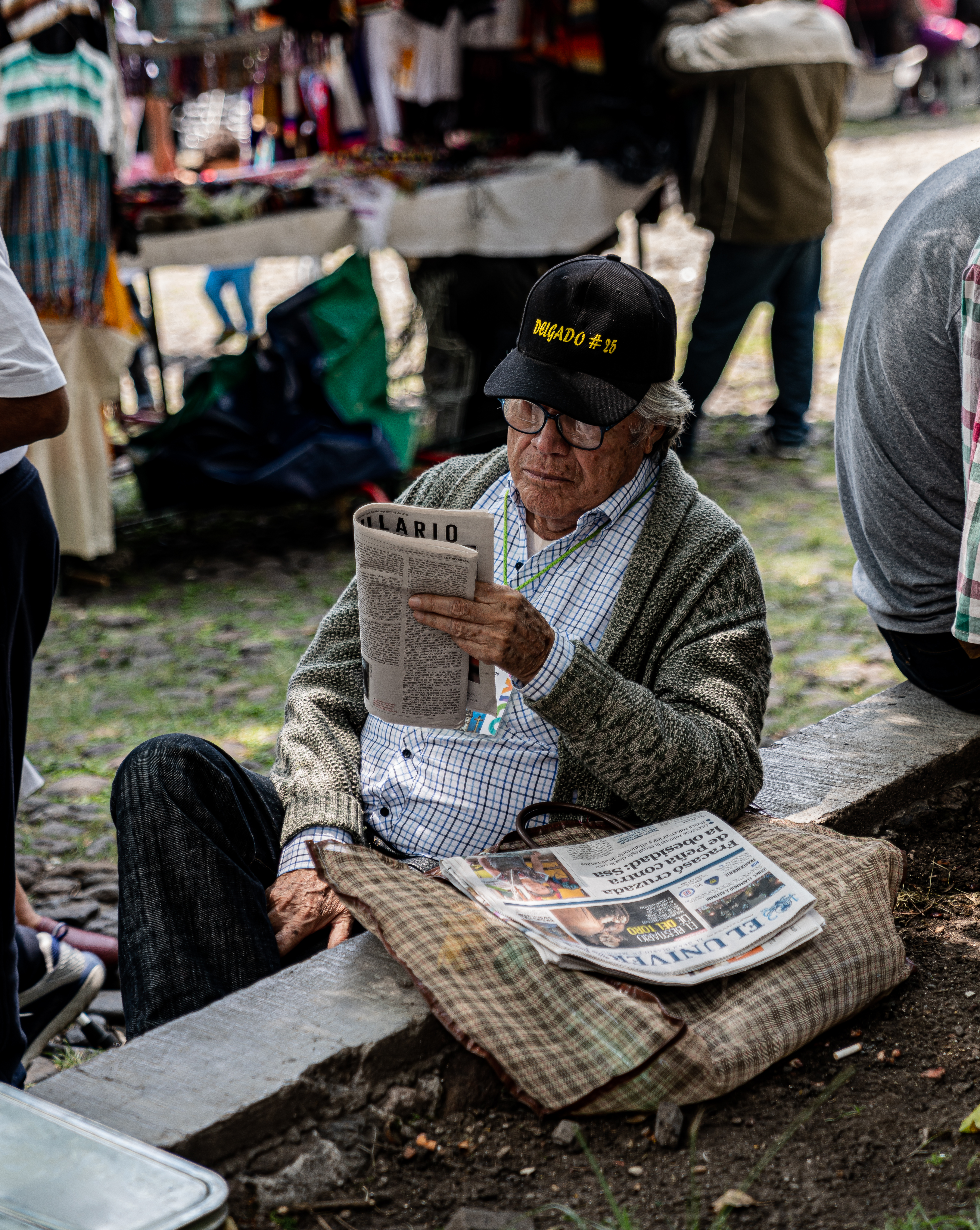 man reading newspaper by stall at daytime
