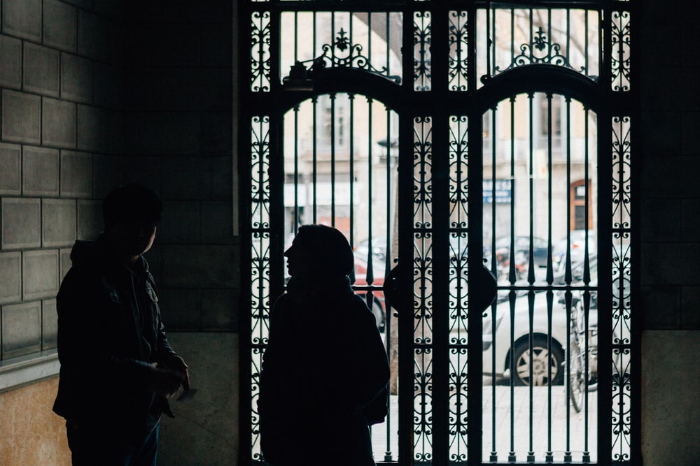 silhouette of two persons standing beside gate