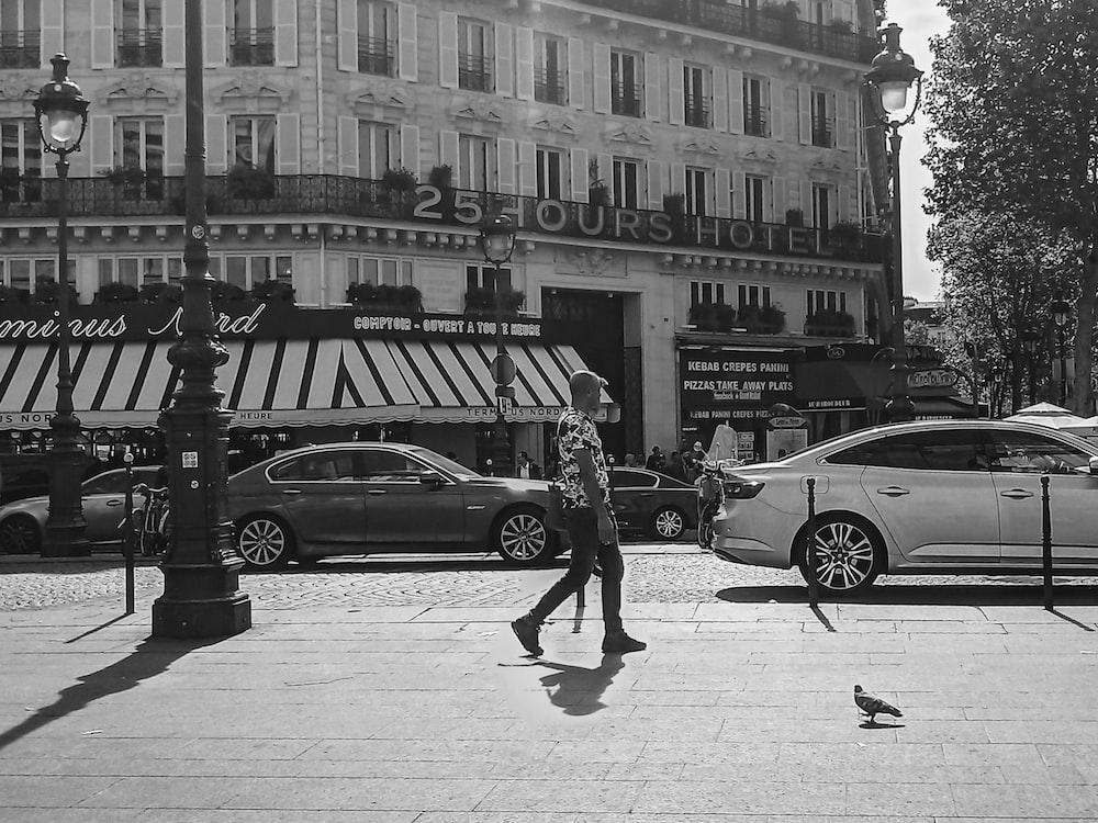 greyscale photography of man walking beside vehicles