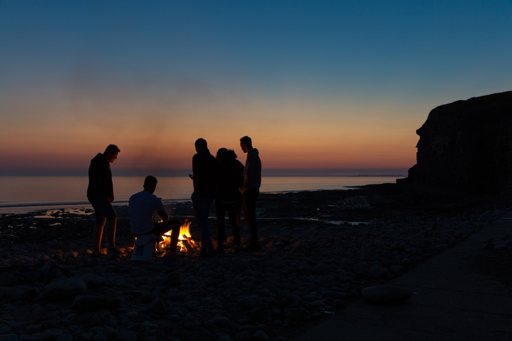 silhouette photography of people gathered around a bonfire by the beach