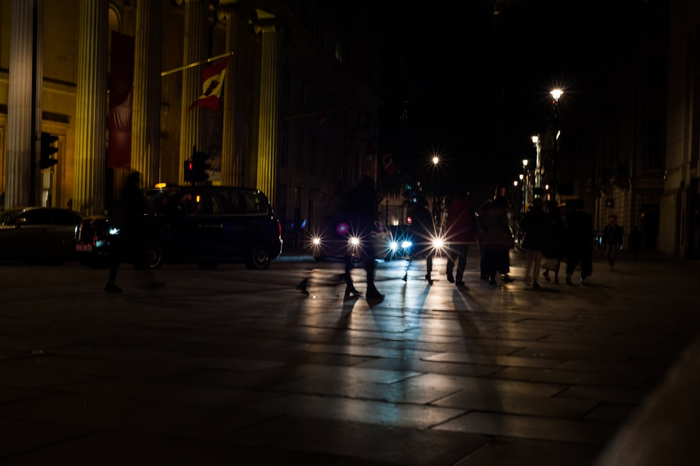 silhouette photography of people crossing a pedestrian lane during nighttime