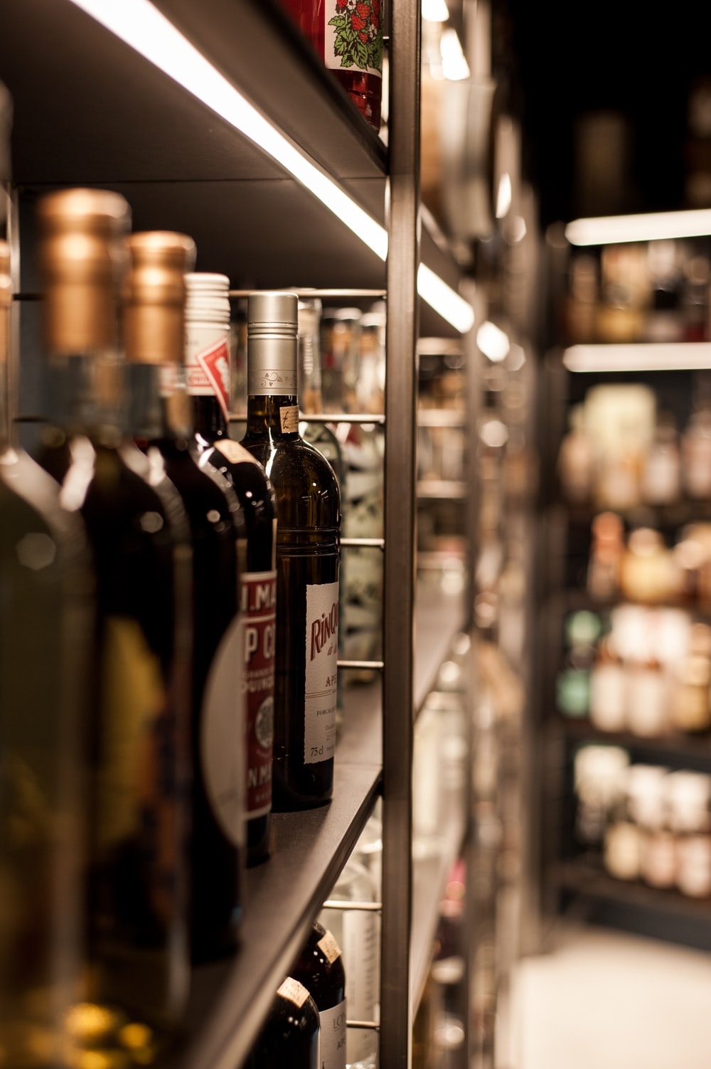 assorted wine bottles display on gray rack