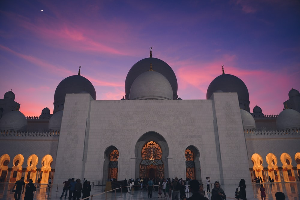 low-angle photography of a prayer temple under a purple sky