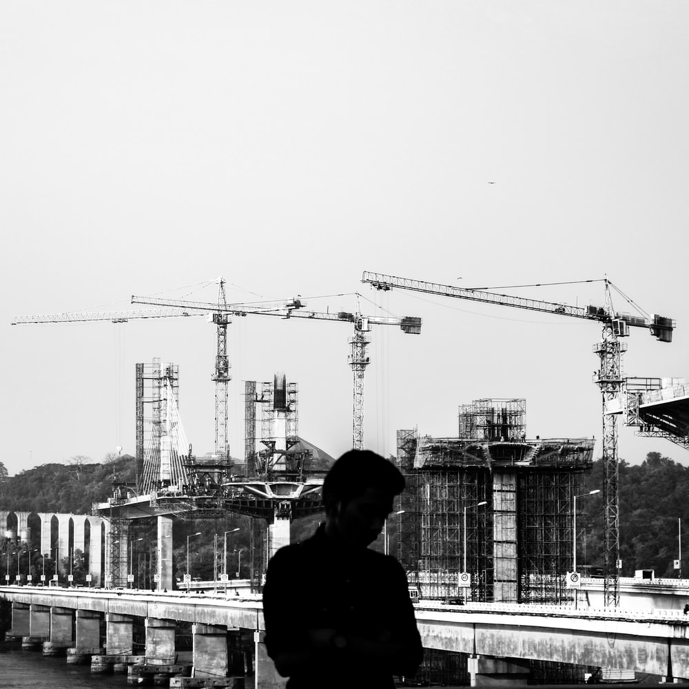grayscale photography of man with a construction site in the background