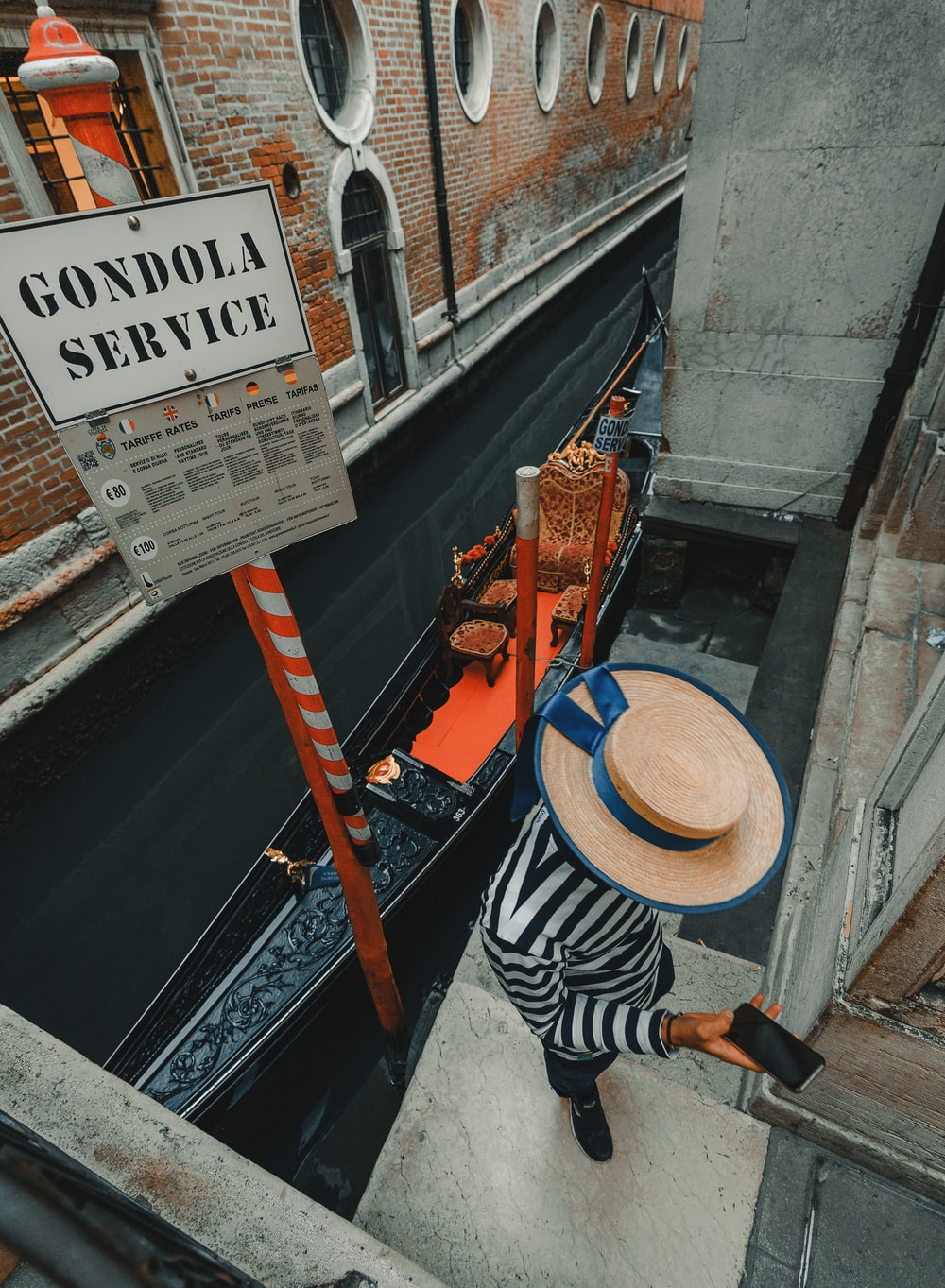 person using phone while standing near Gondola beside Venice canal during daytime