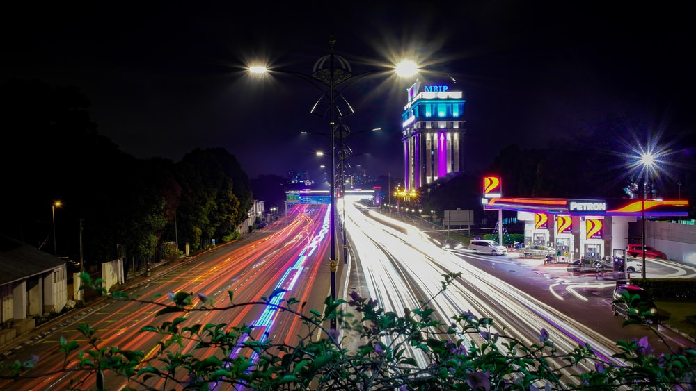 time-lapse photography of moving vehicles on road at night