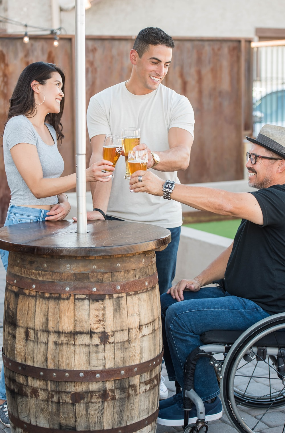 handicapped and couple toss each other of glass of beer