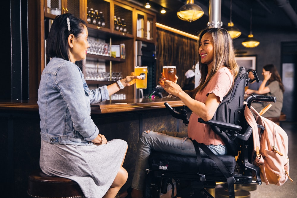 two women about to toss their drinks at the bar