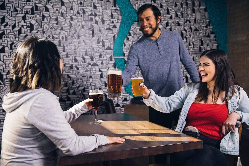 three people drinking beer