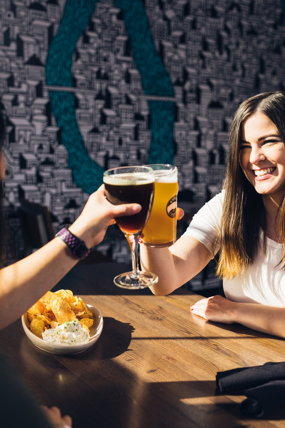 smiling woman sitting on chair while holding beer glass