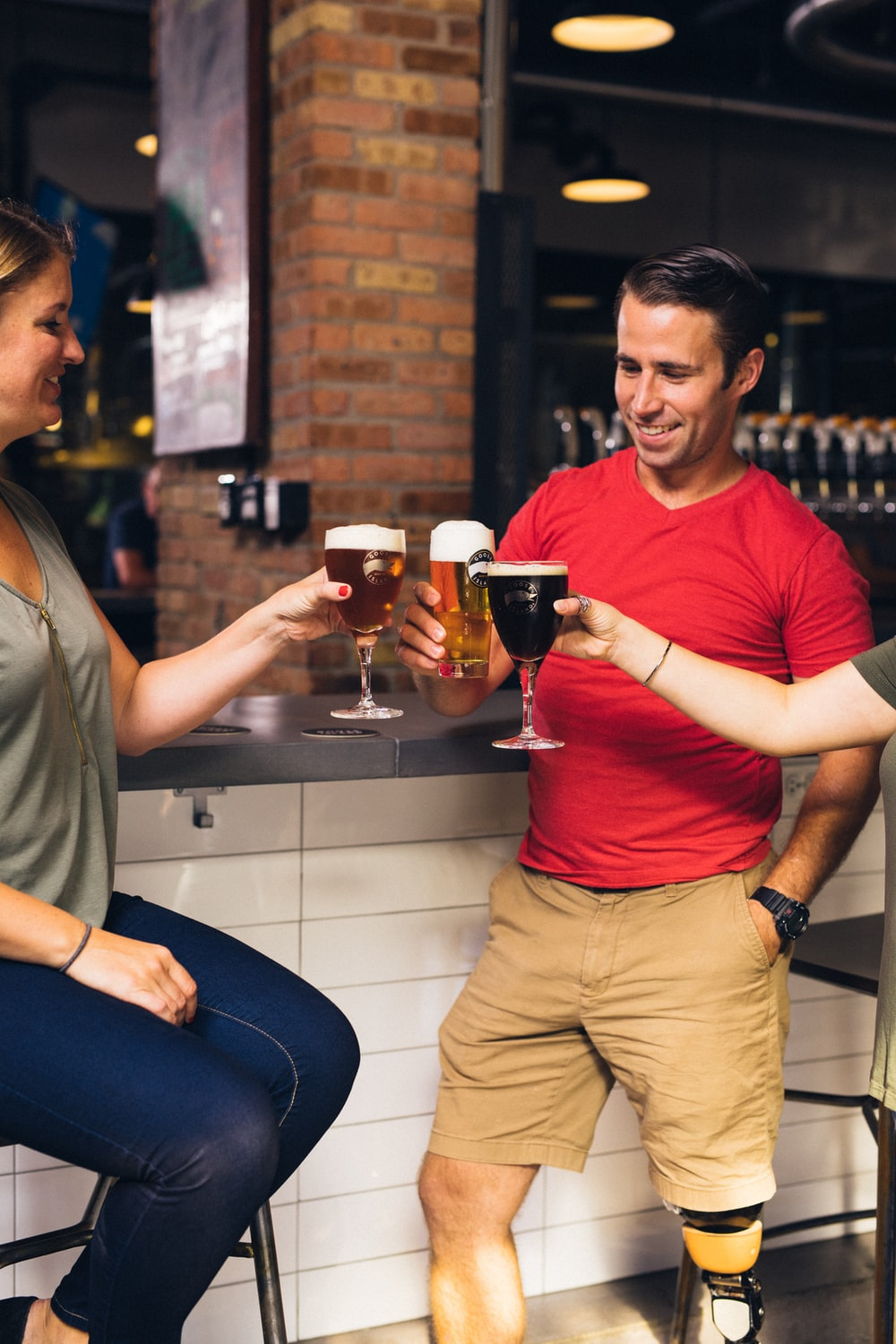 woman sitting on bar stool near another two person toasting beer