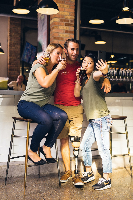 man between two women taking selfie