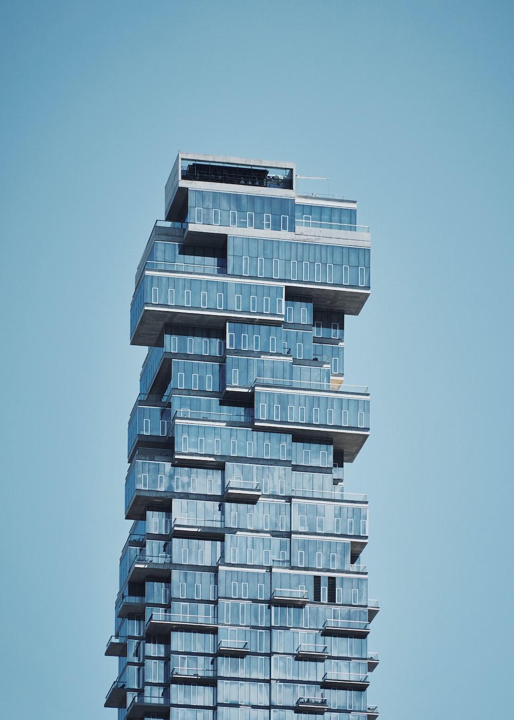 blue high-rise building under a calm blue sky