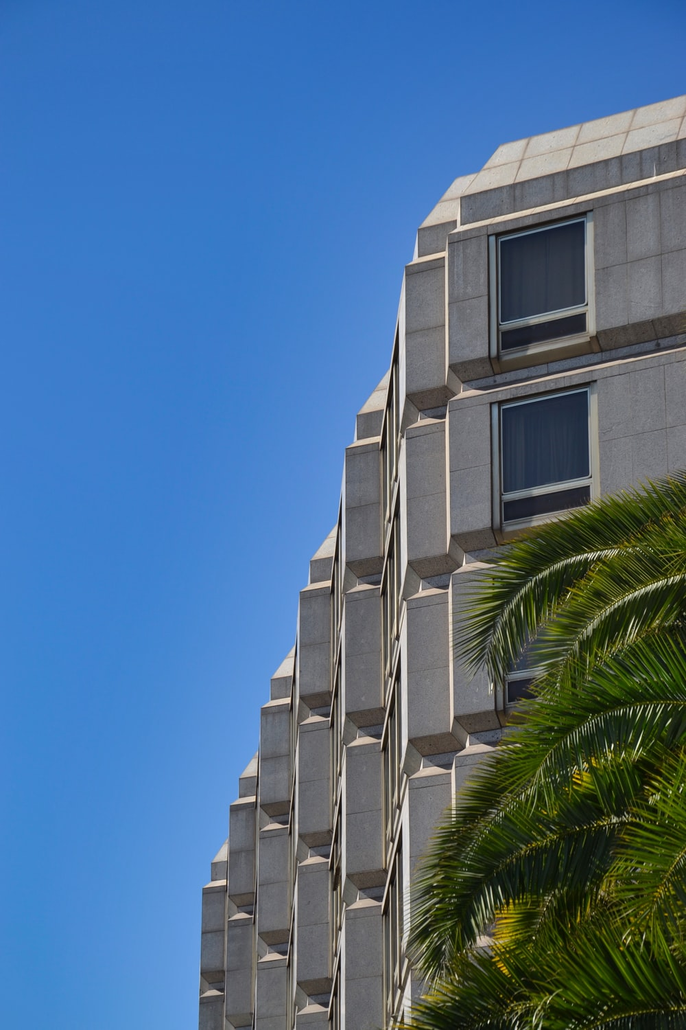 low-angle photography of gray concrete building under blue sky
