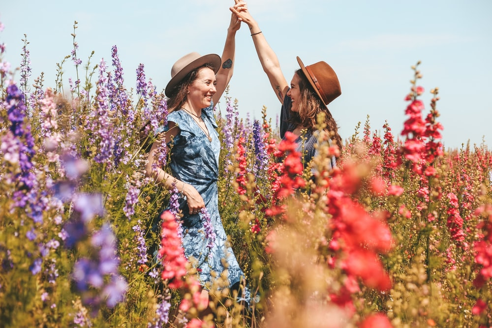 two women holding hands at the flower field