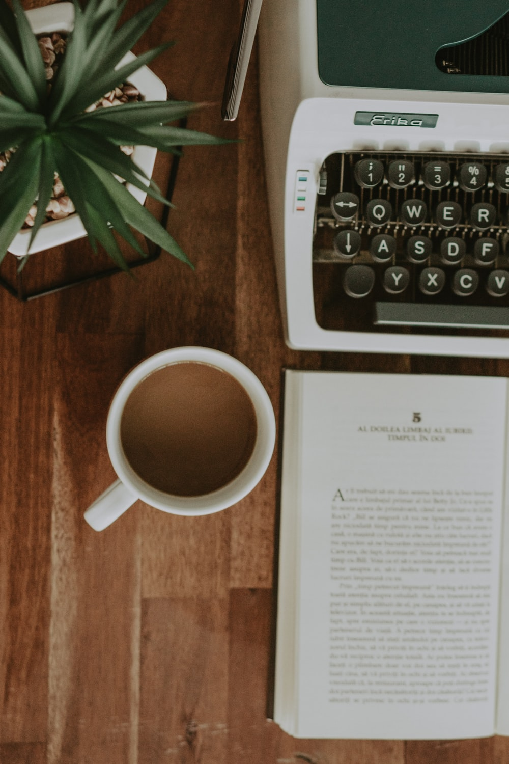 flat-lay photography of cup of coffee beside book and typewriter
