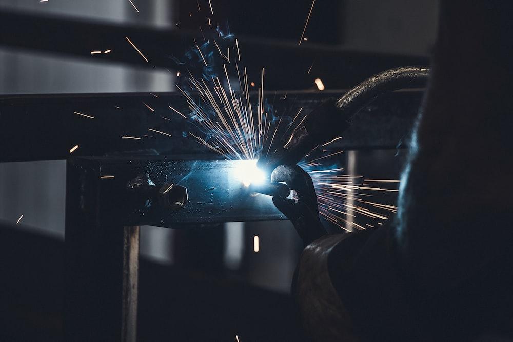 person welds metal