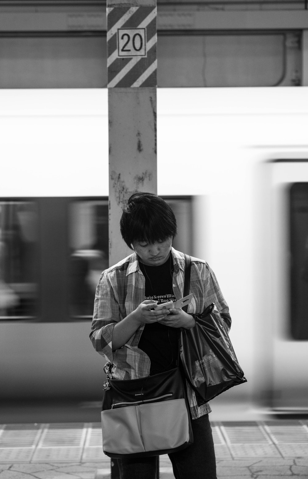 grayscale photography of man using phone while standing