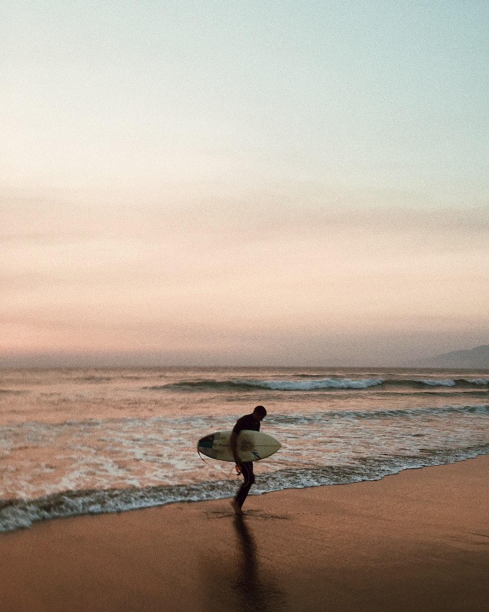 man carrying surfboard on seashore