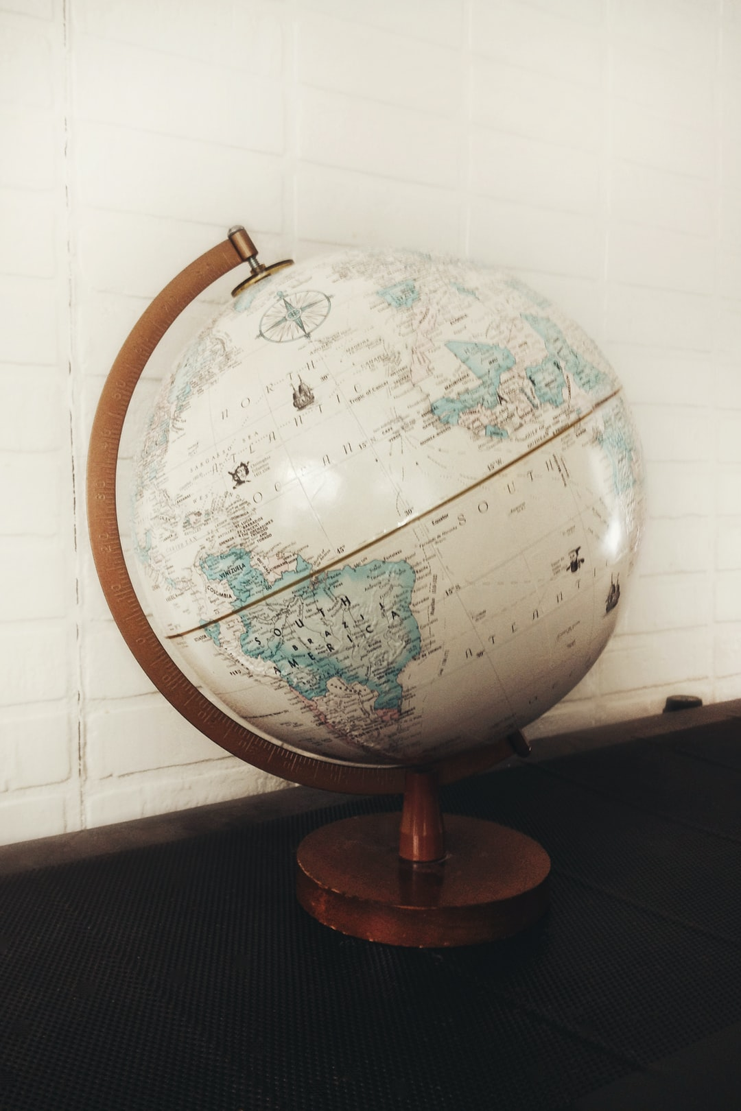 Vintage Rand McNally world globe in ivory on midcentury modern wooden stand sits on a metal table with white brick wall in background.
